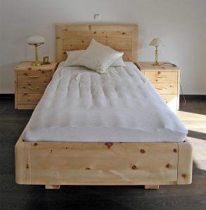 Einzelbett Hocheck, massives Zirbenholzbett, gerahmtes, hohes Kopfhaupt, abgerundete Kanten, Bettkorpus schwebend auf zurückgesetzten Bettfüßen, Abb. mit zwei optionalen, passenden Nachkästchen ebenfalls mit abgerundeten Kanten an Deckplatte und Korpus - Original Steiner Zirbenbett
