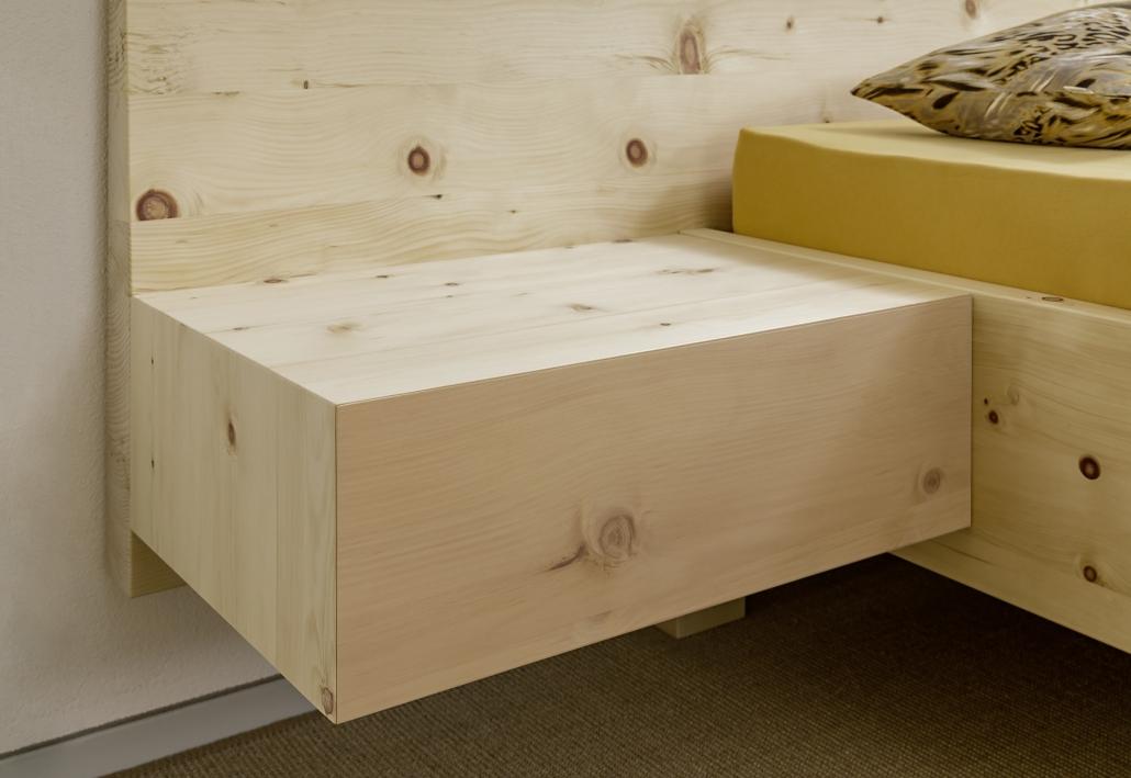 Freischwebend angesetzte, grifflose Nachtkästchen mit Astfront prägen die kompakte, klar geschnittene Form des Doppelbetts Spitzstein - Original Steiner Zirbenbett