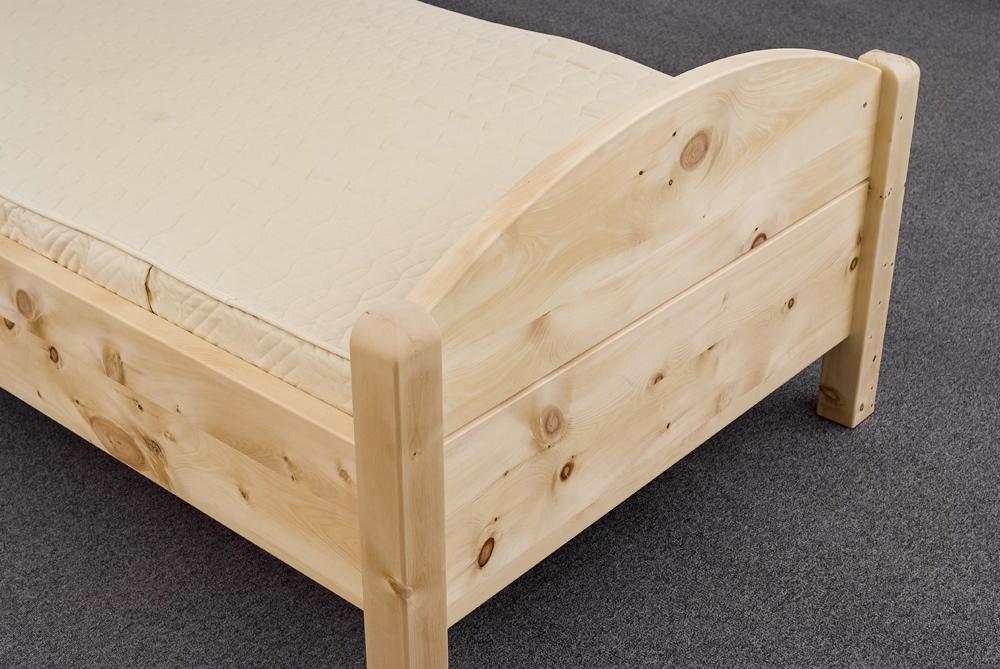Fußhaupt mit flachem Segmentbogen am Einzelbett Breitenstein aus massiver Alpenzirbe, Bettpfosten oben gerundet - Original Steiner Zirbenbett