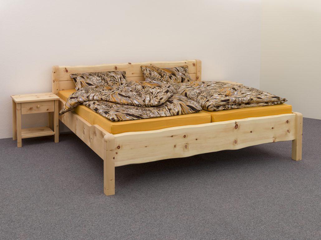 Doppelbett Brünnstein, massives, klassisches Zirbenbett, naturnahe Ausführung mit unbesäumter Waldkante an Kopfhaupt und Fußwange - Abb. mit Deko-Bettware und optionalen Nachttkästchen