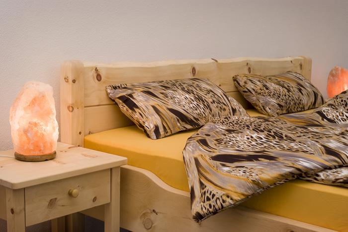 Im Mittelteil abgesenkte Seitenwange und optionales Nachtkästchen am Zirbenbett Brünnstein, Abb. mit Deko-Bettware und Leuchten - Original Steiner Zirbenbett