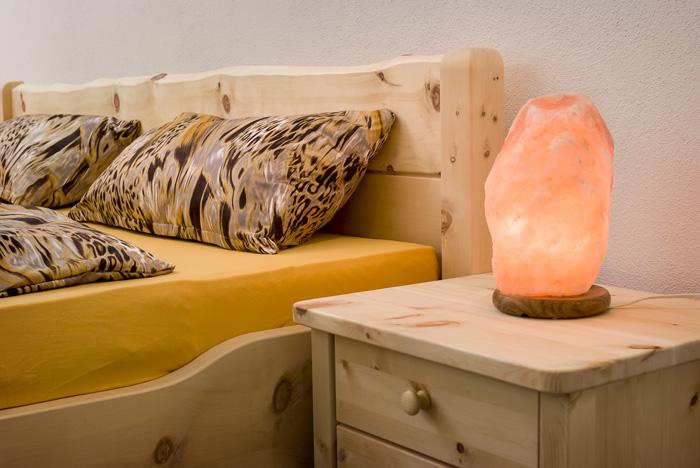optionales Nachtkästchen ergänzt das naturnah ausgeführte Zirbenbett Brünnstein, Abb. mit Deko-Bettware und Leuchten - Original Steiner Zirbenbett