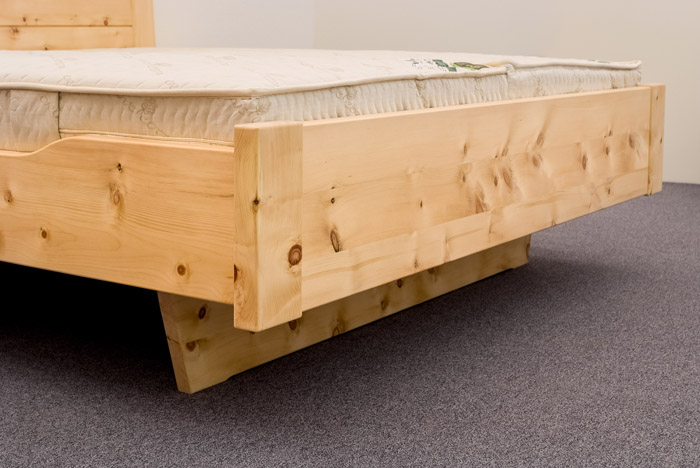 Abgesenkte Seitenwange für leichteren Ein- und Ausstieg, sowie schwebender Fußbereich auf zurückgesetztem Unterbausockel für Doppelbett Kranzhorn - Original Steiner Zirbenbett