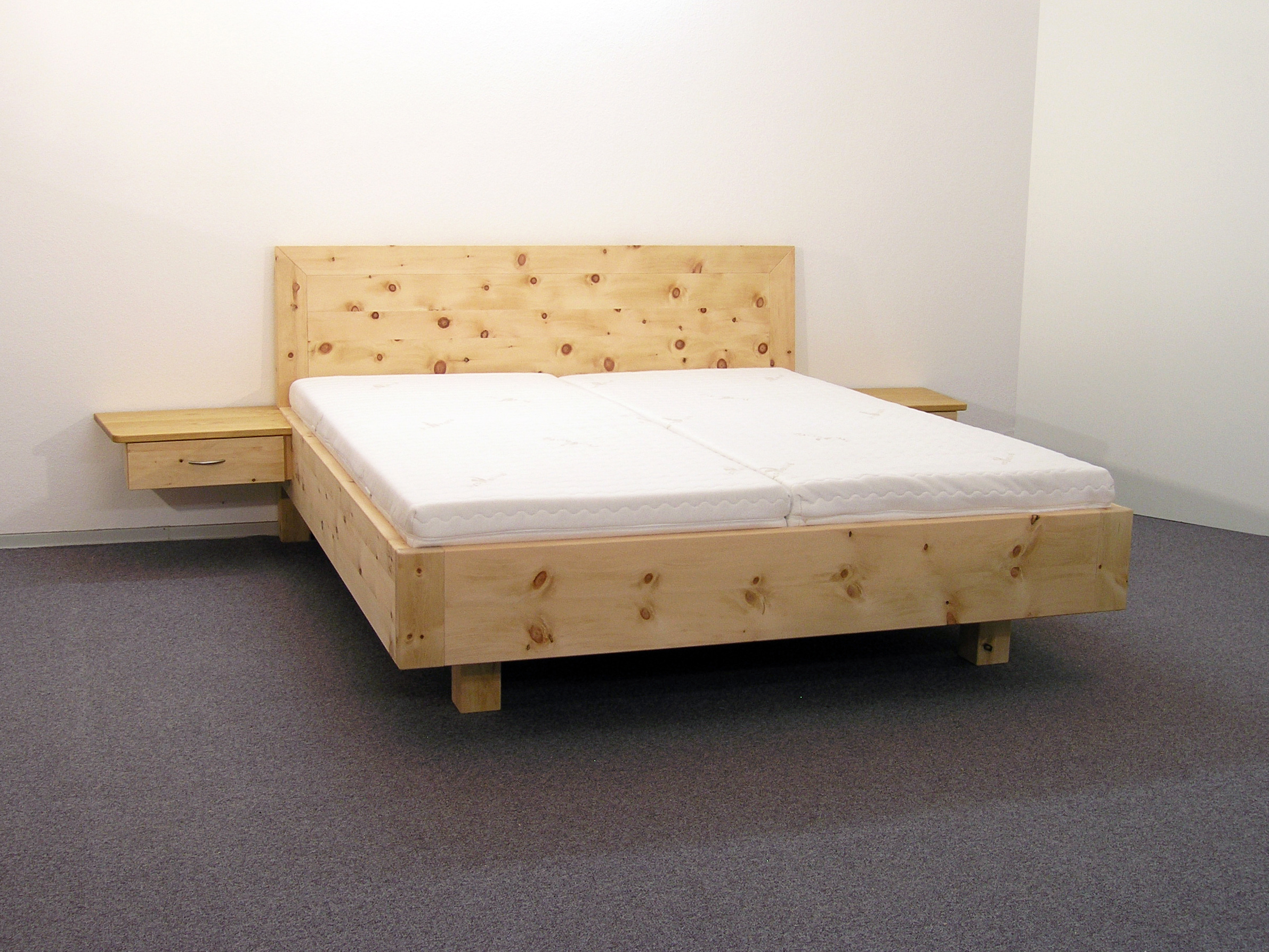 Abb.: Doppelbett Kranzhorn, Zirbenbett-Variante mit freischwebend angesetzten Nachttischen mit Schubladen, Fußbereich auf zurückgesetzten Bettfüßen - Original Steiner Zirbenbett