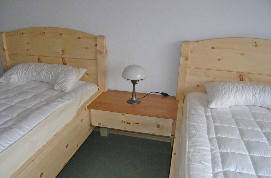 Schwebendes Zirbenholz-Nachtkästchen mit Deckplatte aus geöltem Kirschbaum verbindet die beiden Einzelbetten-Modelle Kranzhorn - Original Steiner Zirbenbett