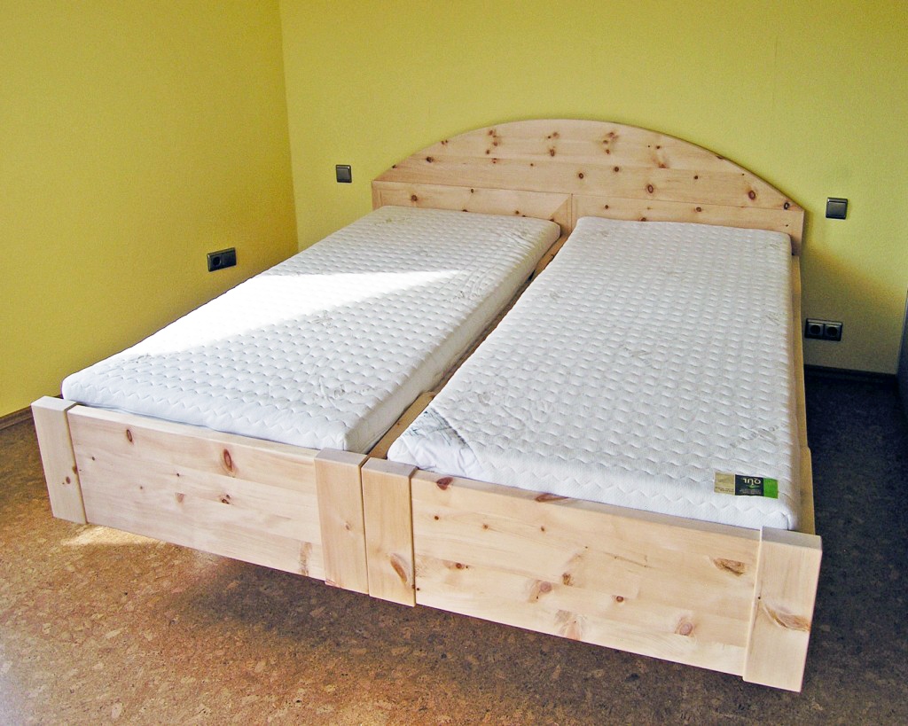Einzelbett Kranzhorn aus Zirbenholz, der aufgesetzte, abnehmbare Segmentbogen verbindet die beiden Einzelbetten zum Doppelbett, Abb. mit optionalem ergonomischen ProNatura-Schlafsystem - Original Steiner Zirbenbett