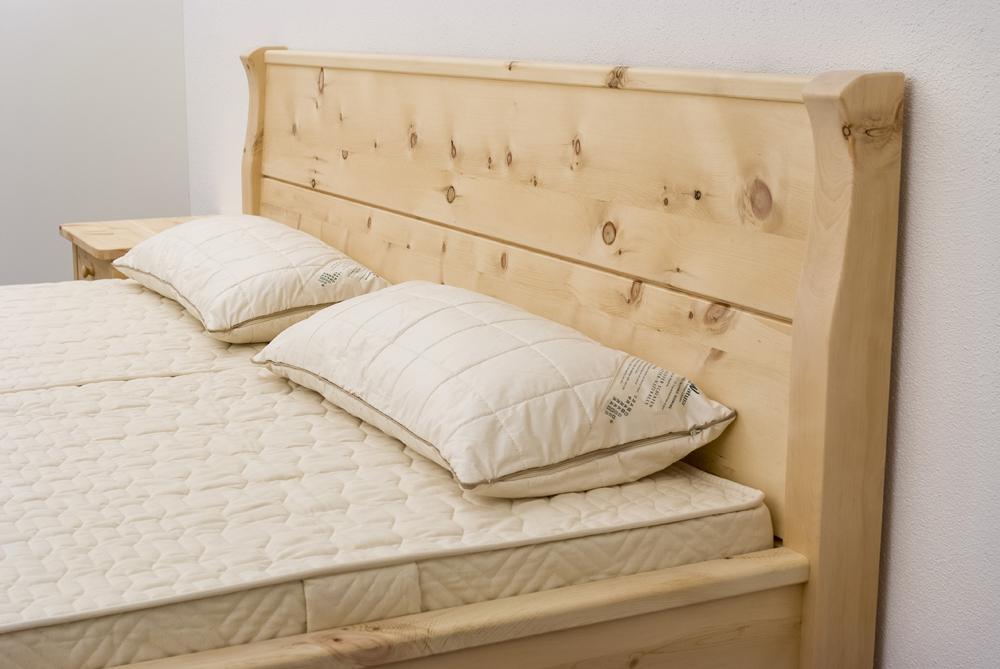 Hochgezogene, geschwungene Bettpfosten und leicht schräge Rückenlehne am Kopfhaupt des Zirbenbetts Rotwand - Original Steiner Zirbenbett