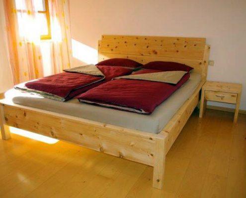 Abb.: Klassisches Zirbenbett Samerberg, Aufsatzleisten an Fußteil und Seitenwangen, verlängerte Bettpfosten am Kopfhaupt - Original Steiner Zirbenbett