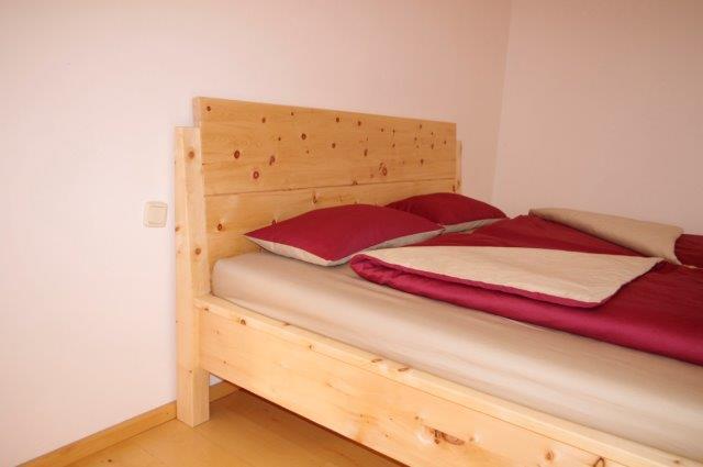 Abb.: Kopfhaupt ohne Aufsatzleisten und hochgezogene Bettpfosten am Doppelbett Samerberg - Original Steiner Zirbenbett