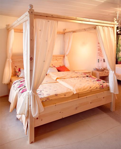 Romantisches Himmelbett Schwarzenberg aus massiver Alpenzirbe, hohe Bettpfosten, umlaufender, profilierter Aufsatz mit Zirbenkugeln auf den Bettpfosten - Original Steiner Zirbenbett