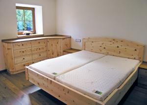 Eck-Kommode aus Tiroler Alpenzirbe, kombiniert mit Eichenholz-Auflageplatte, Maßanbau an Zirben-Nachkästchen und Original Steiner Zirbenbett Kranzhorn, Doppelbett mit Segmentbogen