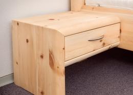 Eleganter, angesetzter Nachttisch mit Vollauszug, geschlossene Seitenwange mit abgerundeten Kanten am Original Steiner Zirbenbett Hocheck