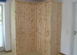 Zirbenholz-Kleiderschrank 09.3, Eckschrank aus massivem Zirbenholz, abgerundete Korpuskanten und abgerundetes Gesims, 4 Türen, abgeplattete Füllungen, Aluminium-Bügelgriffe, Ecktüren öffnen im weiten 155 Grad-Winkel, passend zu Original Steiner Zirbenbetten