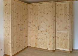 Zirbenholz-Kleiderschrank 09.6, Eckschrank aus massiver Zirbe, abgeschrägte Korpuskanten, gerades Aufsatzgesims, Eichen-Sockel, 5 Rahmentüren mit abgeplatteten Füllungen, 1 Türelement zurückgesetzt, passend zu Original Steiner Zirbenbetten