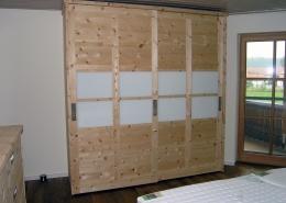 Zirbenholz-Kleiderschrank 06.1 aus massivem Zirbenholz. 2 Schiebetüren in Rahmenbauweise mit Griffmulden. Dreigeteilte Türfronten, im Mittelteil mit Milch-Glaseinsätzen, passt u.a. sehr gut zu unserem Original Steiner Zirbenbett Kranzhorn